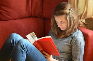 a college girl is reading a book