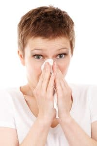 a woman is sneezing