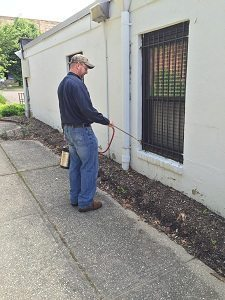 an exterminator is spraying insects around a house